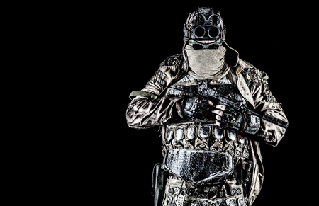 Post apocalyptic world bandit or marauder, nuclear disaster survivor, veteran stalker in face mask and sunglasses, handicraft lamellar armor, armed with handmade pistol, isolated on black studio shoot Reklamní fotografie - 105914124