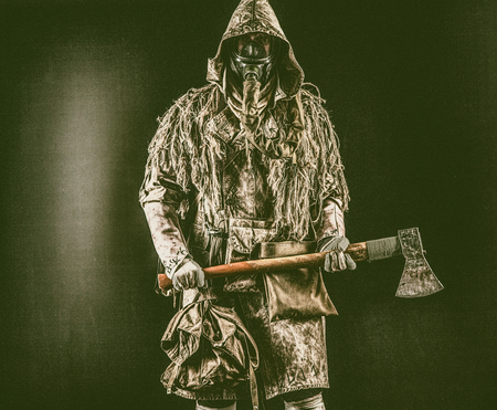 Post apocalyptic survivor, radioactive zone stalker, crazy serial killer or maniac in gas mask and tattered clothes decorated with runes, threatening with raised ax isolated on black studio shoot Zdjęcie Seryjne