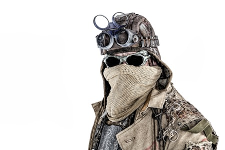 Close up portrait of nuclear doomsday survivor, post apocalyptic world marauder with face hidden behind sackcloth mask and sunglasses, wearing tattered rags and junk, isolated on white with copyspace Stock Photo
