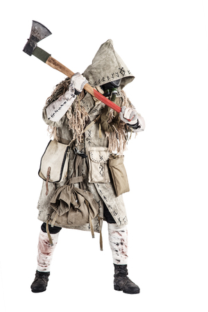Post apocalypse world survivor, bandit or marauder in gas mask, ghillie cape, ragged clothes with runes, showing beckoning sign while standing with carpenters axe in hand, isolated on white shoot Reklamní fotografie - 105914232