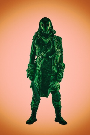 Terrifying post apocalyptic human creature, person survived in poisoned by pollution, post nuclear catastrophe world wearing tatters and full-face gas mask isolated on white background studio shoot Reklamní fotografie - 105914440