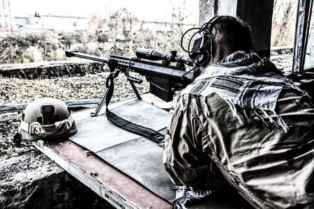 Portrait of U.S. Navy SEAL sniper on firing position, armed with large caliber sniper rifle with telescopic sight, wearing tactical headset with microphone, observing territory, searching targets