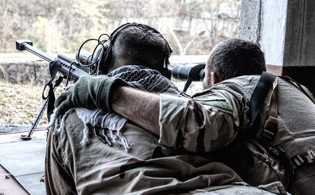 Military snipers team spotter observing battlefield, searching targets with binoculars, holding arm on shooters shoulder, correcting snipers fire with anti-materiel sniper rifle from hidden position Archivio Fotografico