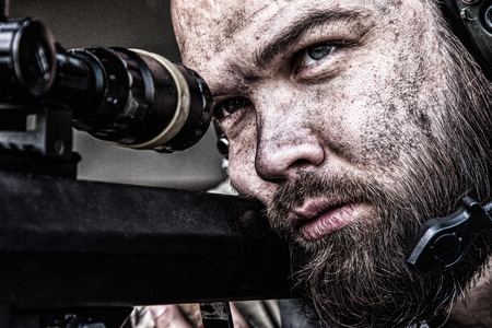 Army sniper with bearded, dirty face aiming with optical telescopic sight on sniper rifle, observing battlefield from ambush and searching targets to shoot, shooting on long range distances, close up Archivio Fotografico