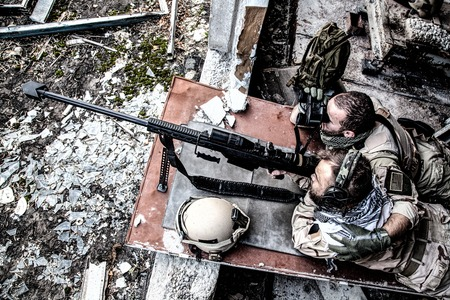United States Navy SEAL sniper team firing with large caliber, anti material sniper rifle with optical sight from ruined, abandoned building. Elite members of anti-terrorist squad in modern warfare 版權商用圖片