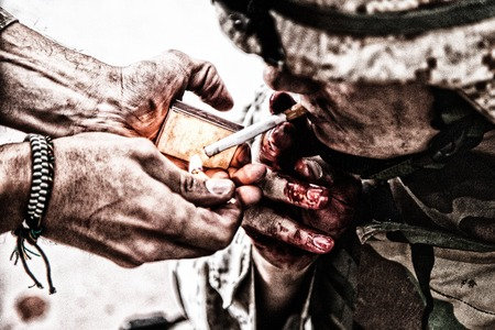 Wounded army soldier, tired military medics with fingers in blood, lighting cigarette with burning match in comrade palms. Psychological pressure, emotional trauma, post-traumatic disorder on war