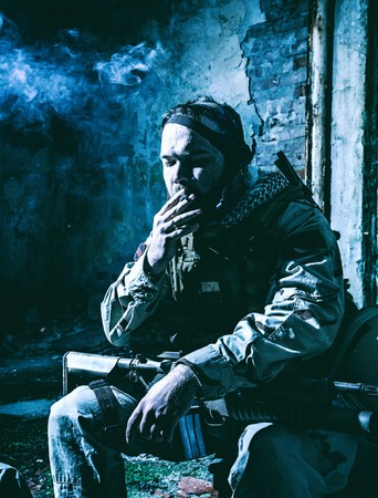 Tired after hard battle army soldier, exhausted with fight Navy Seal rifleman sitting with assault rifle on knees, resting and smoking cigarette in abandoned building, low key, high contrast shoot Stock Photo