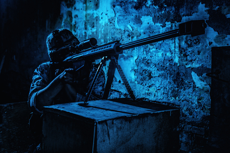 Army sniper night ambush in ruined building. Marine rifleman aiming with optical opscore and shooting in darkness with large caliber, anti-materiel sniper rifle. Secret military mission, urban warfare