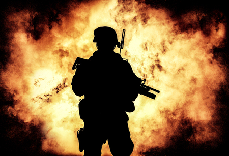 Silhouette of modern infantry soldier, elite army fighter in tactical ammunition and helmet, standing with assault service rifle in hands Stock Photo