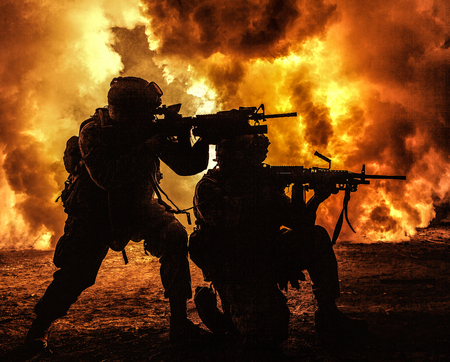 Silhouettes of two army soldiers, U.S. marines team in action, surrounded fire and smoke, shooting with assault rifle and machine gun, attacking enemy with suppressive gunfire during offensive mission Stock Photo