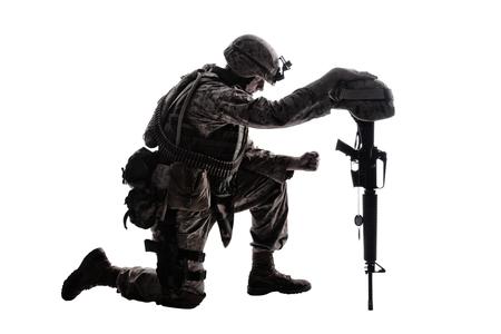 Żołnierz armii w smutku za poległego towarzysza, stojąc na kolanach, oparty na karabinie z hełmem i dwoma nieśmiertelnikami na łańcuchu, studio strzelać na białym niskim kluczu sylwetka. Wojskowe odznaczenia pogrzebowe, żal za zabitych w akcji