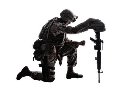 Army soldier in sorrow for fallen comrade, standing on knee, leaning on rifle with helmet and two dog tags on chain, studio shoot isolated on white low key silhouette. Military funeral honors, grief for killed in action