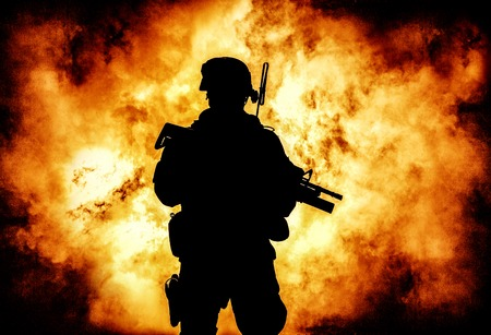 Silhouette of modern infantry soldier, elite army fighter in tactical ammunition and helmet, standing with assault service rifle in hands on background of fiery explode. Burning fire of war conflict