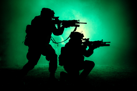 Silhouettes of two army soldiers, U.S. marines team in action, surrounded fire and smoke, shooting with assault rifle and machine gun, attacking enemy with suppressive gunfire during offensive mission Imagens