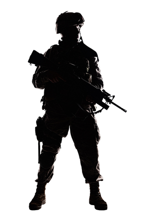 Full length, low key studio shoot of fully equipped army soldier in camo uniform and helmet, armed with pistol and assault service rifle with underbarrel grenade launcher isolated on white background Stock Photo