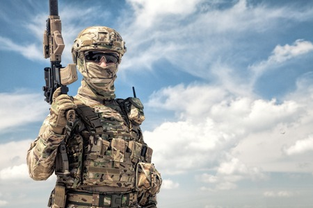 Half-length portrait of airsoft game player in army camouflage uniform, tactical helmet, load carrier and face hidden behind mask, posing with firearm replica in hands, cloudy sky on background