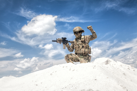Airsoft military games player in camouflage uniform and helmet armed assault rifle replica, sitting on knee on top of sand dune with sky on background and showing freeze hand signal to his teammates