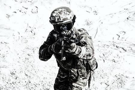 Jugador de airsoft con uniforme de combate de camuflaje, protegido con casco y anteojos balísticos, apuntando con mira óptica a la réplica de rifle de servicio militar en zona arenosa. Participante de juegos de guerra