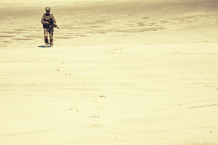 Lone army soldier in uniform, with service carbine in hands walking through hot sands desaturated, sepia tone. Military intervention or campaign in Middle East region, armed conflict in desert area