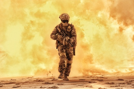 Army soldier in military camouflage uniform, helmet, with face hiding behind mask and glasses, running out from fire. Infantry rush with fire support, commando attack and breakthrough on battlefield