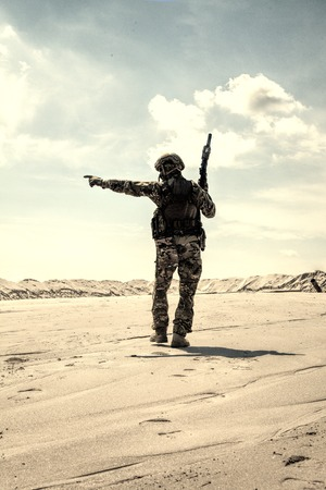 Soldier of special forces, infantry rifleman in military ammunition walking in desert and pointing on horizon. Military reconnaissance team leader managing dead ground observation with combat patrol Reklamní fotografie