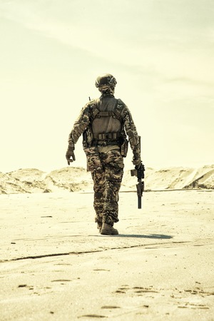 Military contractor, army infantry or rifleman in camouflage uniform and helmet patrolling territory in desert. Airsoft player with real firearm replica walking in sandy area desaturated, back view