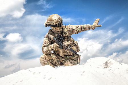 Army soldier or airsoft player in camo uniform and helmet, armed assault rifle, standing on knee on sand dune, looking back and showing halt or stop hand signal. Nonverbal communication on battlefield Imagens - 114685008