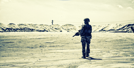 Special operations forces soldier, private military company mercenary or security armed with service rifle patrolling and observing protected territory in sandy desert area, back view, desaturated