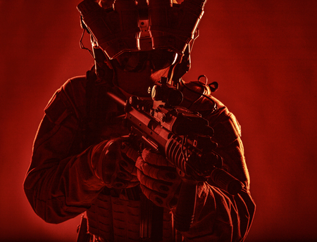 Special operations forces soldier, counter terrorism assault team fighter with night vision device on helmet and red dot laser sight on service rifle, low key studio shoot silhouette with backlight Stock Photo
