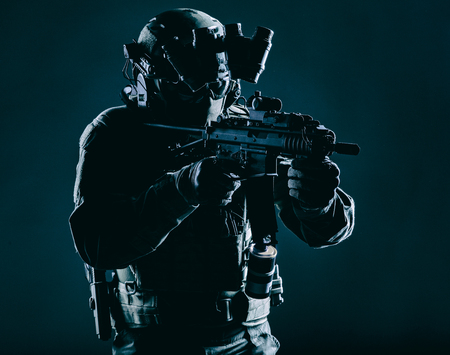 Army special operations squad soldier, police counter terrorism assault team member, security service rifleman in mask, helmet with headset and night vision device, armed short barrel service rifle