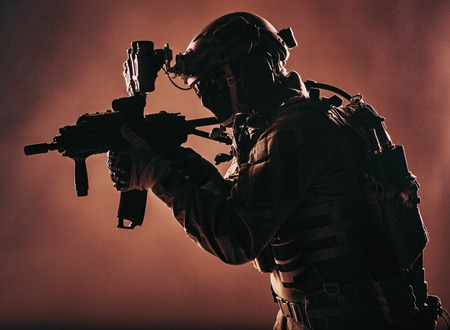 Army soldier, counter terrorist squad fighter, military company mercenary in ammunition and body armor, helmet with night vision device, aiming with short barrel service rifle, low key, studio shoot