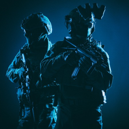 Two members of army elite forces, counter terrorism squad soldiers in battle uniform with modern tactical ammunition, armed service rifles, standing together shoulder to shoulder, low key studio shoot