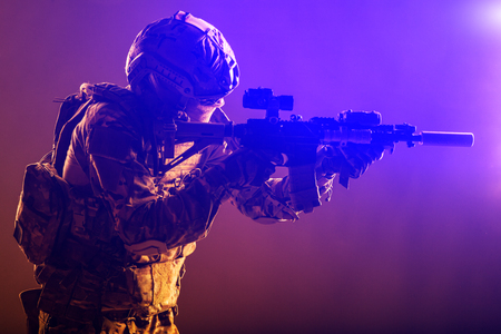 Modern soldier of army special forces, police anti-terrorist squad fighter in battle uniform, helmet with night vision device aiming short barrel assault rifle, low key studio shoot with red backlight Banco de Imagens