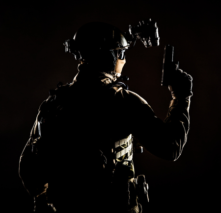 Army elite forces soldier, police special operation, counter terrorist team member in tactical ammunition with hidden behind mask identity, standing backwards with pistol in hand, low key studio shoot