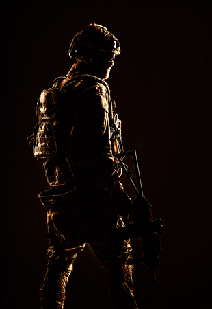 Low key studio shoot of army special forces soldier, commando fighter in mask, ballistic glasses, tactical helmet and battle uniform, holding short barrel service rifle, looking back over shoulder