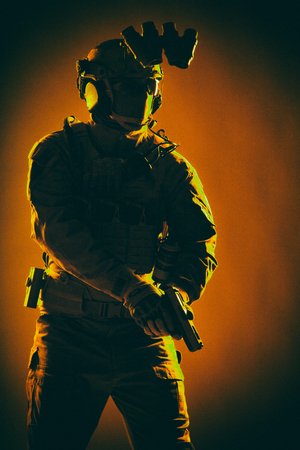 Anti terrorist squad fighter, army elite forces soldier in mask, with night vision device and tactical radio headset on helmet, armed service pistol standing ready for action, low key studio shoot Stock Photo