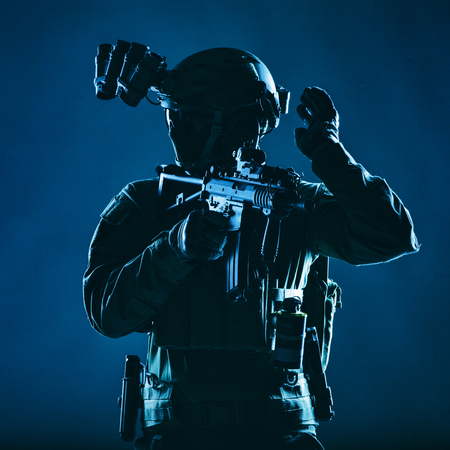 Special operations soldier, SWAT team fighter in mask and glasses, equipped night vision device, armed short barrel service rifle, looking back and showing freeze hand signal, low key studio shoot Banco de Imagens - 115911395