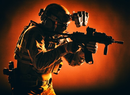 Modern soldier of army special forces, police anti-terrorist squad fighter in battle uniform, helmet with night vision device aiming short barrel assault rifle, low key studio shoot with red backlight Stok Fotoğraf