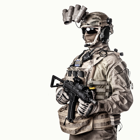 Army elite soldier with hidden behind mask and glasses face, in full tactical ammunition, equipped night vision device, radio headset, armed short barrel service rifle studio shoot on white background