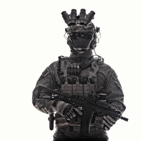 Half length studio portrait of anti-terrorist squad fighter, special operations soldier, military company mercenary in tactical ammunition with night vision device, armed short barrel assault rifle Banco de Imagens