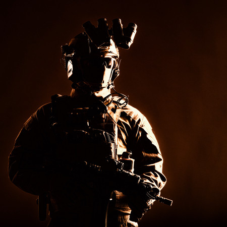 Army elite forces member, modern infantryman with hidden face, in tactical ammunition, equipped radio headset, night vision device mounted on helmet, standing with short barrel service rifle in hands Banco de Imagens - 115911447