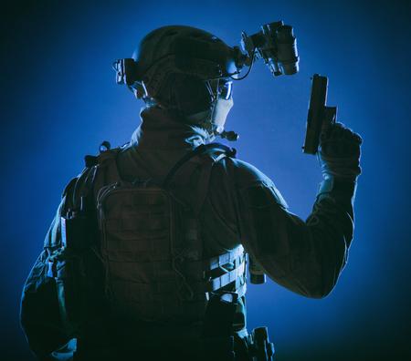 Soldat des forces d'élite de l'armée, opération spéciale de la police, membre de l'équipe antiterroriste en munitions tactiques avec identité cachée derrière un masque, debout à l'envers avec un pistolet à la main, tournage en studio discret