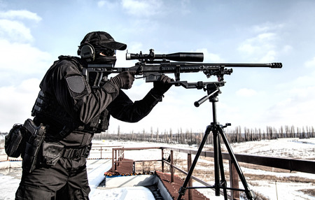 Equipped police SWAT sniper shooting with rifle Banco de Imagens