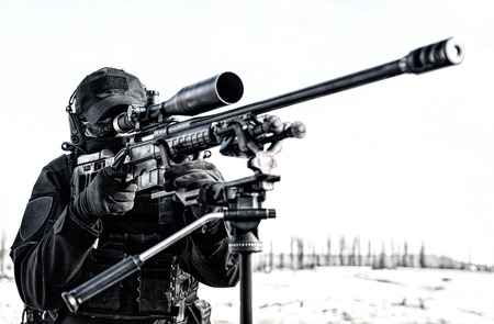 Equipped police SWAT sniper shooting with rifle Stock Photo