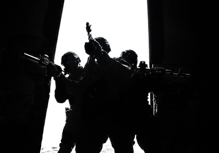 Groupe d'opérations spéciales de la police franchissant la porte