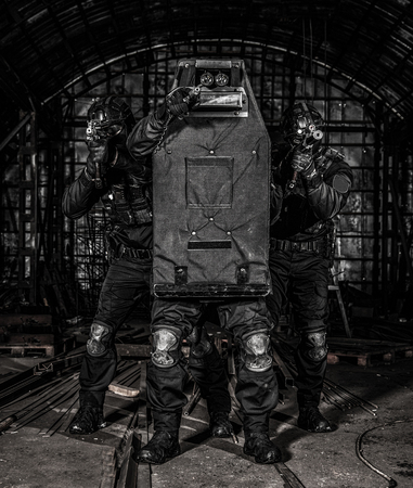 SWAT team members covering with ballistic shield