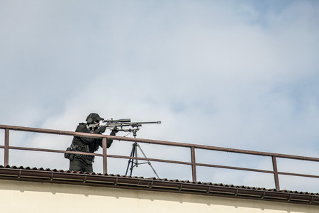 Police sniper aiming with optical sight from roof Zdjęcie Seryjne