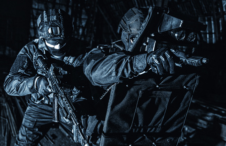 Police SWAT unit hiding behind ballistic shield