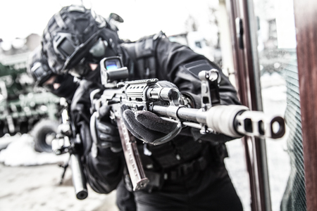 Police special reaction team member aims with gun Stock Photo