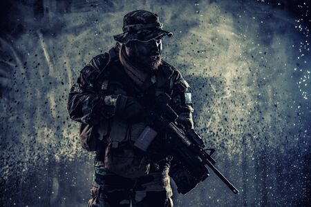 Commando fighter with rifle sneaking in darkness